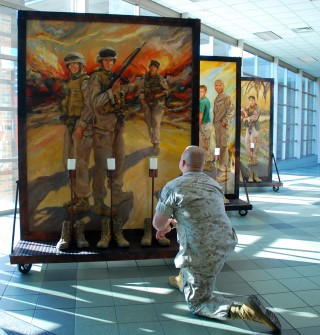 Soldier kneeling before one of the display panels in The Eyes of Freedom display.